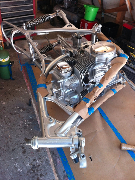 I use the HondaTwins.Net trick of laying the engine down and installing the frame over the engine - much easier than trying to get the engine in the frame while it is upright on its wheels